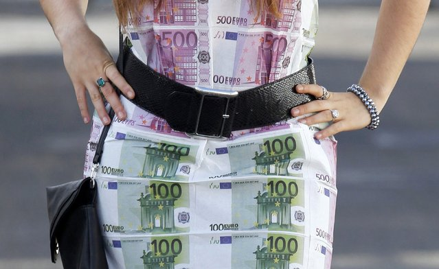A woman wears a home-made dress featuring imitation 100 and 500 euro notes as she walks in Bordeaux, southwestern France, November 7, 2014. The look-alike currency notes, printed on individual pieces of fabric and sewn together to complete the dress were also used in other projects by the creator including tabelcloths. (Photo by Regis Duvignau/Reuters)