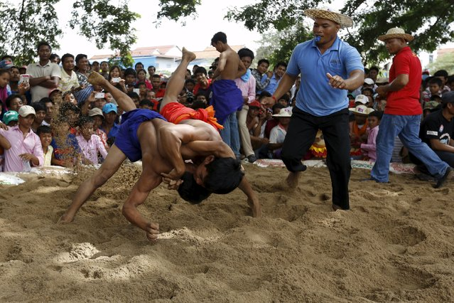 Men wrestle during during a religious festival at Virhear Sour village in Kandal province, Cambodia, October 12, 2015. (Photo by Samrang Pring/Reuters)