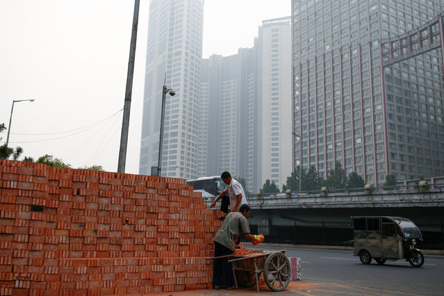 Workers load a cart with bricks at a construction site in Beijing, China, September 16, 2016. (Photo by Thomas Peter/Reuters)