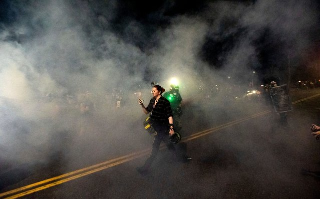 A woman walks through smoke during the 100th consecutive day of demonstrations in Portland, Ore., as police use chemical irritants and crowd control munitions to disperse protesters on Saturday, September 5, 2020. (Photo by Noah Berger/AP Photo)