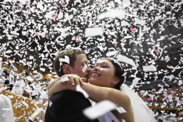 A newlywed couple celebrates during a mass wedding ceremony of the Unification Church at Cheongshim Peace World Centre in Gapyeong, about 60 km (37 miles) northeast of Seoul February 17, 2013. The Unification Church founded by evangelist reverend Moon Sun-myung in Seoul in 1954, performed its first mass wedding in 1961 with 33 couples. Approximately 3,500 couples attended the mass wedding on Sunday. (Photo by Kim Hong-Ji/Reuters)