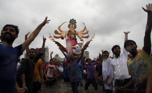 Devotees prepare to immerse an idol of elephant-headed Hindu god Ganesha in the Arabian Sea after worship marking the end of the 10-day long Ganesh Chaturti festival in Mumbai, India, Thursday, September 15, 2016. (Photo by Rajanish Kakade/AP Photo)