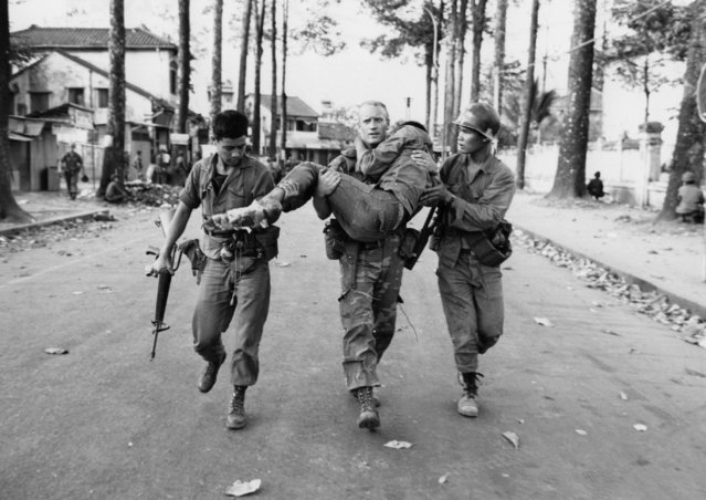 In his February 6, 1968, file photo, First Lt. Gary D. Jackson of Dayton, Ohio, carries a wounded South Vietnamese Ranger to an ambulance after a brief but intense battle with the Viet Cong during the Tet Offensive near the National Sports Stadium in the Cholon section of Saigon. Early on the morning of Jan. 31, 1968, as Vietnamese celebrated the Lunar New Year, or Tet as it is known locally, Communist forces launched a wave of coordinated surprise attacks across South Vietnam. The campaign, one of the largest of the Vietnam War, led to intense fighting and heavy casualties in cities and towns across the South. (Photo by Dang Van Phuoc/AP Photo)