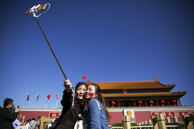 Girls take a selfie at the Tiananmen Gate as they celebrate National Day marking the 66th anniversary of the founding of the People's Republic of China in Beijing October 1, 2015. (Photo by Damir Sagolj/Reuters)