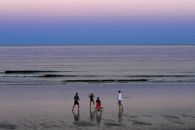 A group of people play Spikeball at twilight on the beach, Thursday, August 7, 2020, in Ocean Park, Maine. As the summer tourist season reaches its peak Maine's coronavirus positivity rate remains among the lowest in the nation. (Photo by Robert F. Bukaty/AP Photo)