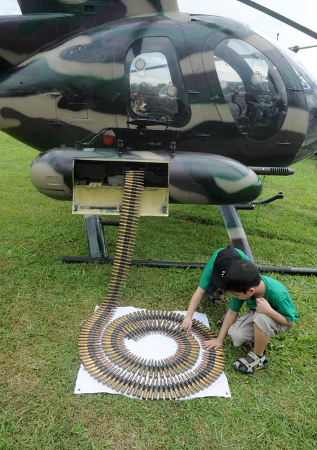 Children play with 50 caliber ammunition from an attack helicopter at Camp Aguinaldo in suburban Manila on November 16, 2014. Military equipment was on display to celebrate the 75th founding anniversary of the Department of National Defence (DND). (Photo by Jay Directo/AFP Photo)