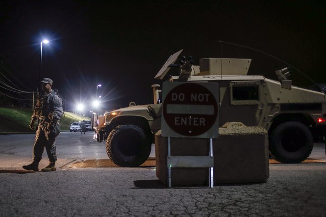 A member of the National Guard stands along a parked military vehicle in the back of a shopping center in Ferguson, Missouri November 24, 2014. Missouri Governor Jay Nixon urged people in the St. Louis area to show respect and restraint following a grand jury's decision on whether to criminally charge a white police officer in the August fatal shooting of unarmed black teenager Michael Brown. (Photo by Adrees Latif/Reuters)