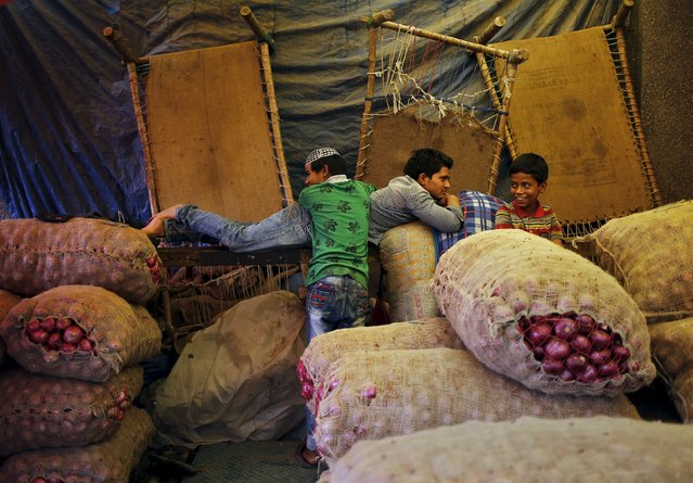 People rest next to stacked sacks of onions at a wholesale vegetable market in New Delhi, India, October 14, 2015. (Photo by Anindito Mukherjee/Reuters)