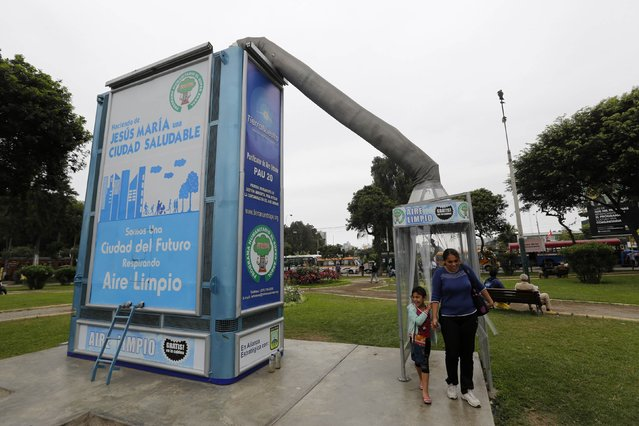 "People leave a giant air purifier, which its inventor calls a ""super tree"", in Lima's district of Jesus Maria November 24, 2014. In Peru's notoriously polluted capital Lima, local inventor Jorge Gutierrez, a retired naval engineer, is deploying the giant air purifiers that double as billboards to suck up carbon dioxide and dangerous levels of smog. (Photo by Mariana Bazo/Reuters)"