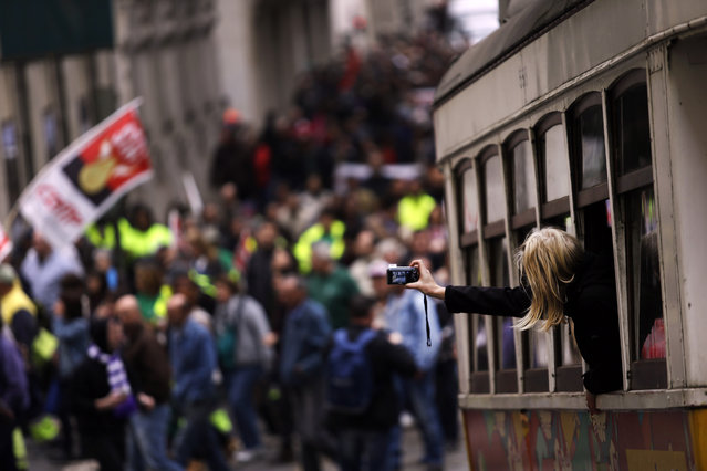 A woman takes photographs from inside a tram as people march during a protest by Portugal's main union General Confederation of Portuguese Workers, CGTP, in Lisbon, Tuesday, November 25, 2014. The protest was against the 2015 state budget proposed by the center-right coalition government. (Photo by Francisco Seco/AP Photo)