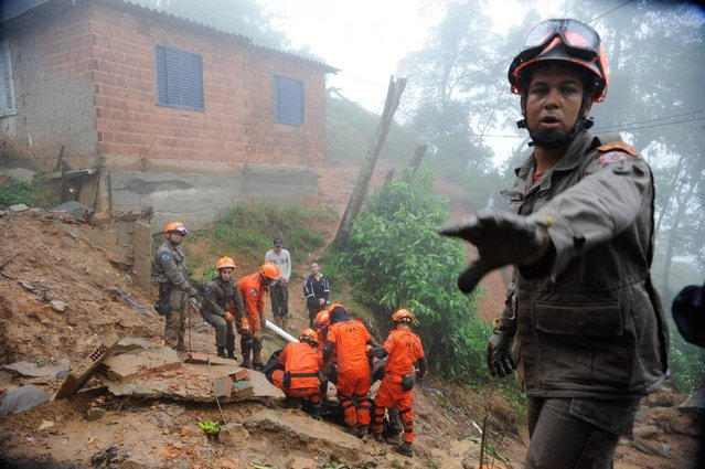A rescue worker gestures as his colleagues carry the body of a victim of a mudslide in Petropolis, near Rio de Janeiro, March 18, 2013. Heavy rains that battered Petropolis on Sunday have killed at least 13 people according to local media. (Photo by Tania Rego/Reuters/Agencia Brasil)
