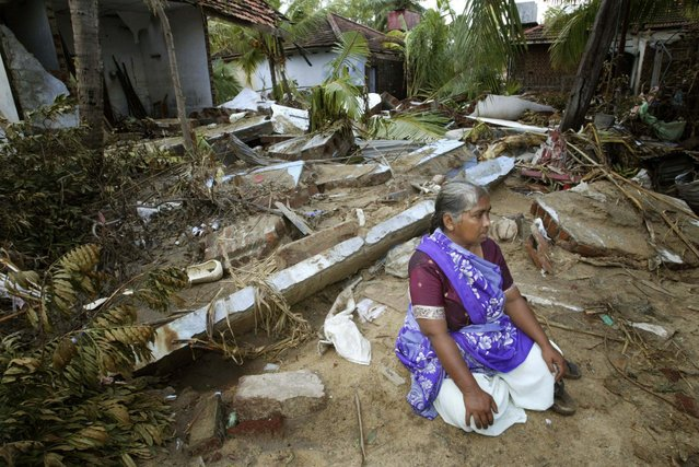 A Sri Lankan woman sits in front of her destroyed house in Kalmunai in this December 30, 2004 file photo. (Photo by Thomas White/Reuters)