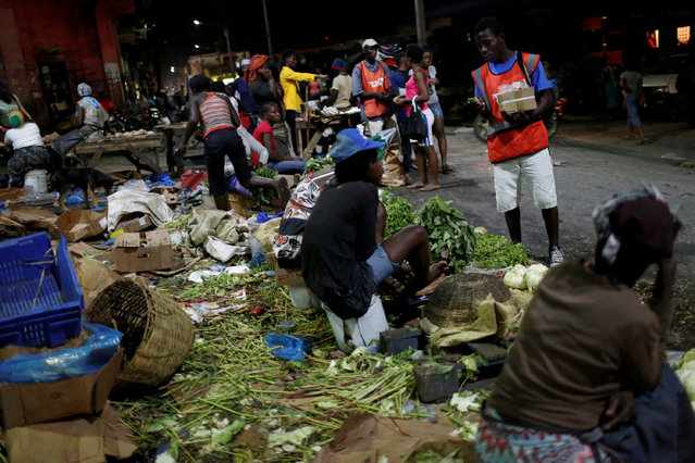 Vendors sell their goods at a street market while Hurricane Matthew approaches in Port-au-Prince, Haiti, October 2, 2016. (Photo by Carlos Garcia Rawlins/Reuters)