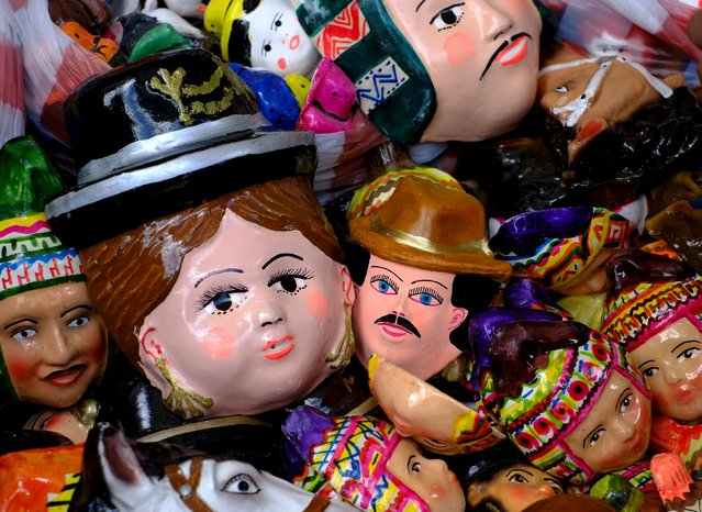 Masks that come with T'antawawas bread are displayed in a popular market of La Paz, October 27, 2015. Residents of La Paz city have started to prepare offerings for their dead relatives next Sunday as part of the All Saints' Day celebrations. The offerings include things the deceased liked during their life, such as fruits, food, breads and drinks, according to local media. (Photo by David Mercado/Reuters)
