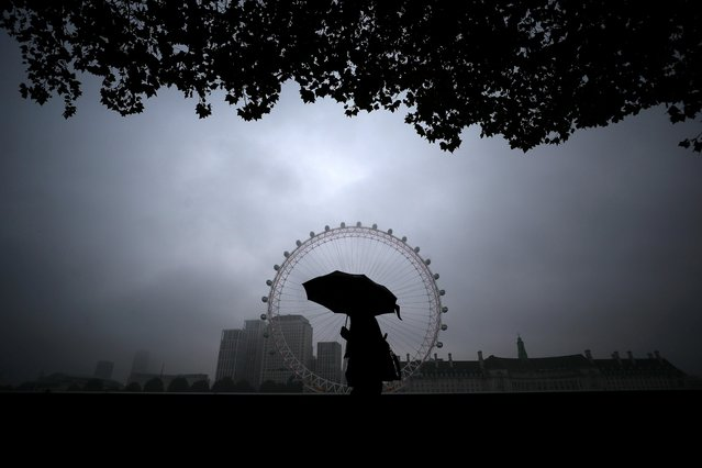 A person shelters under an umbrella as they walk past the London Eye in London, Britain on September 29, 2020. (Photo by Hannah McKay/Reuters)