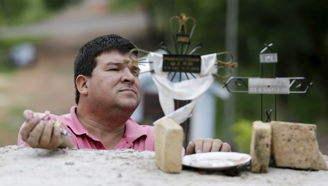 A man is seen at the cross of the grave of a relative at a cemetery during the observance of All Souls' Day in Asuncion, Paraguay, November 2, 2015. (Photo by Jorge Adorno/Reuters)