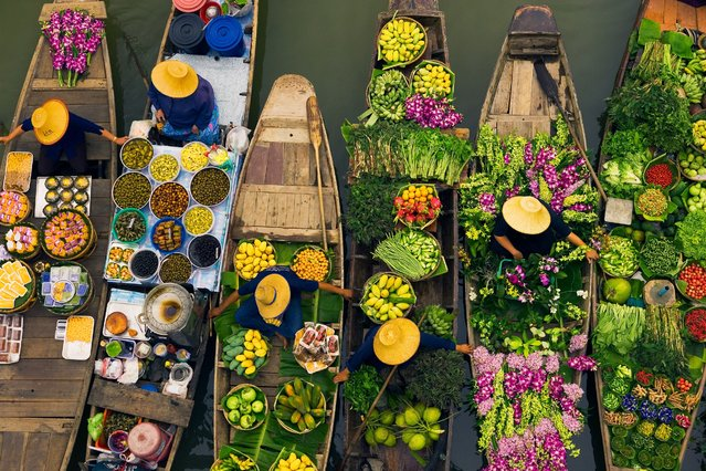 """Floating markets are a common tradition throughout Southeast Asia where the numerous rivers and waterways are a primary means of transportation and commerce between villages. In this overhead view, Bangkok vendors draw their boats together to exchange a colorful, tasty array of goods, Thailand"". (Photo by Art Wolfe/Art Wolfe Stock)"