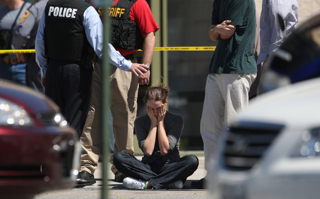 Clara Keller, of Blacksburg, Va. holds her head as she sits on the sidewalk near law enforcement officers outside the New River Valley Mall in Christiansburg, Va. on Friday, April 12, 2013. Officials say two women have been shot at the community college section of the mall and a suspect is in custody. (Photo by Daniel Lin/AP Photo/The Roanoke Times)
