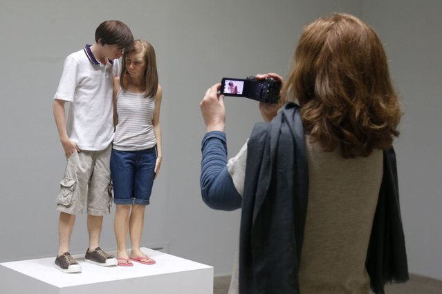 "A visitor looks at a sculpture entitled ""Young Couple, 2013"" by artist Ron Mueck during the press day for his exhibition at the Fondation Cartier pour l'art contemporain in Paris April 15, 2013. The exhibition will run from April 16 to September 29, 2013. (Photo by Charles Platiau/Reuters)"