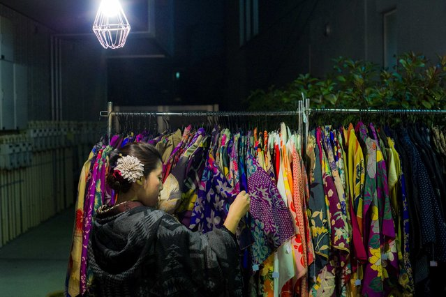 A woman browses through kimonos for sale at Boroichi flea market in Tokyo December 15, 2014. In the 16th century, Boroichi was a place for farmers to buy and sell rags, known as boro, for mending clothes and weaving sandals. Now in its 436th year, the original spirit lingers, with about 700 stands hawking fabric, used clothes and piles of rags. Others sell kitchen tools, pottery, seaweed and spices. (Photo by Thomas Peter/Reuters)
