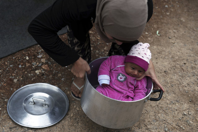 A Syrian mother carries her baby girl in a cooking pot at Ritsona refugee camp north of Athens, Wednesday, October 12, 2016. About 600 people, mostly families with small children, live in tents in the camp, which officials say will soon be replaced by prefabricated homes. (Photo by Petros Giannakouris/AP Photo)