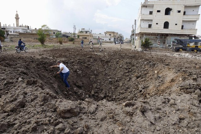 A man walks out of a crater caused by what activists said was a barrel bomb dropped by forces loyal to Syria's President Bashar Al-Assad in the town of Dael, north of Deraa, Syria November 8, 2015. (Photo by Alaa Al-Faqir/Reuters)