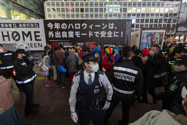 """Police officers and security guards direct bystanders not to pause and stop pedestrian traffic as they try to watch people in Halloween costumes gathered near Tokyo's famed Shibuya traffic intersection Saturday, October 31, 2020. The sign in the background reads, """"Refrain from going out to be safe during this year's Halloween"""". Halloween for Japanese people is simply a fun time, but the city government asked people not to gather because of the pandemic. (Photo by Hiro Komae/AP Photo)"""