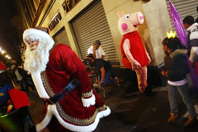 People dressed as Santa Claus and children's character Chanchita Pepa walk on a street, as a man gives a massage to a woman in Mexico City December 23, 2014. (Photo by Edgard Garrido/Reuters)