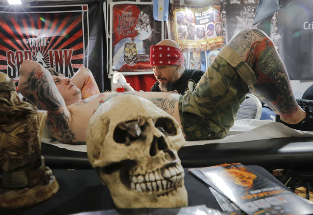 A man gets a tattoo during the International Tattoo Convention Bucharest 2016 in Bucharest, Romania, Sunday, October 16, 2016. Prominent tattoo artists from across the world displayed their skills in the Romanian capital over the weekend. (Photo by Vadim Ghirda/AP Photo)