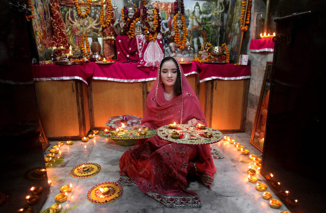 A Pakistani Hindu woman lights candles during Diwali celebrations at a local temple in Lahore, Pakistan, Wednesday, November 11, 2015. Diwali, the festival of lights, is one of Hinduism's most important festivals dedicated to the worship of Lakshmi, the Hindu goddess of wealth. (Photo by K. M. Chaudary/AP Photo)