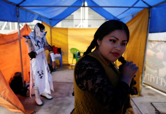 Susana La Bonita, a cholita wrestler, fixes her hair before their fight during their return to the ring after the coronavirus disease (COVID-19) restrictions, in El Alto outskirts of La Paz, December 6, 2020. (Photo by David Mercado/Reuters)