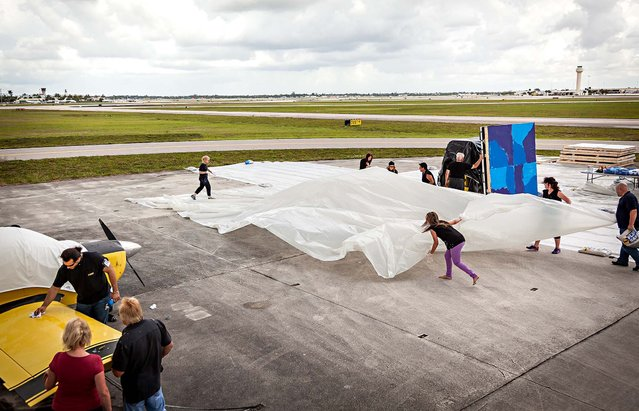 Painting is halted so more plastic tarp can be laid on the tarmac. A small private plane near the painting area was  speckled in blue paint and had to be cleaned before the princess could continue with the multiple canvases planned for the day. (Photo by Thomas Cordy/The Palm Beach Post)