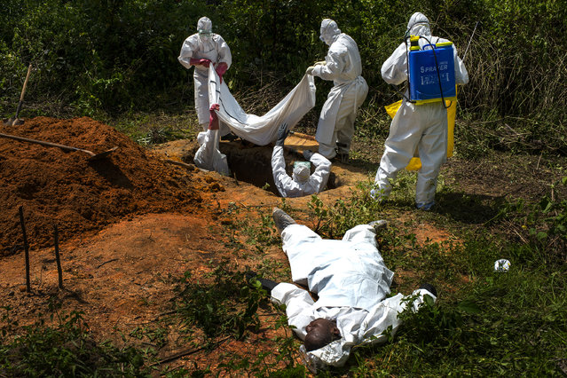 Alexander Morris lays flat on his back after he fainted due to the extreme heat inside a  protective suit, while the Lofa County Health Department team buries his sister, on Friday November 7, 2014 in Voinjama, Liberia. Morris had insisted on accompanying the burial team during the removal and burial of his sister, Jacqueline Morris, 38. (Photo by Michel du Cille/The Washington Post)