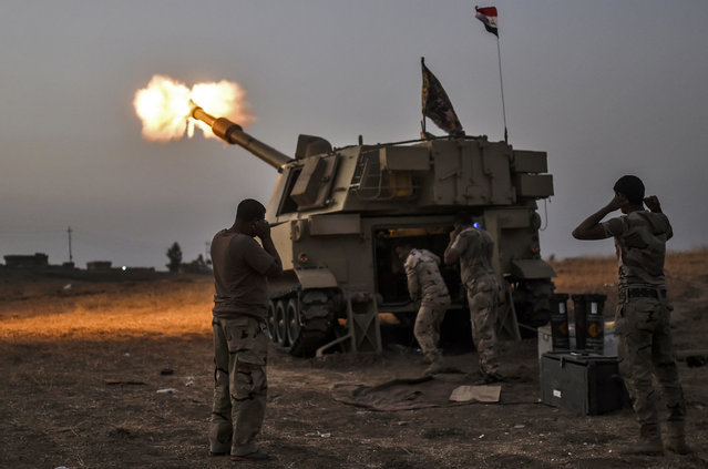 Iraqi forces fire a M109 self-propelled howitzer towards the village of Al-Muftuya from a position in Kani al-Harami, some 35 kilometres of Mosul, on October 19, 2016, during an operation against Islamic State (IS) group jihadists to retake the main hub city. Iraqi forces prepared to retake several key areas around Mosul, including the country's largest Christian town, to tighten the noose on the Islamic State group's stronghold. (Photo by Bulent Kilic/AFP Photo)