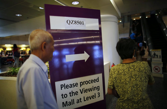 People walk past a sign board instructing relatives and next-of-kin to gather at a holding area at the Changi International Airport where AirAsia flight QZ8501 from Surabaya was scheduled to land, Sunday, December 28, 2014 in Singapore. (Photo by Wong Maye-E/AP Photo)