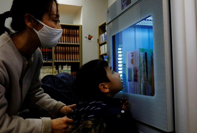 A boy looks at a ultraviolet sterilising machine cleaning library books he rents, amid the coronavirus disease (COVID-19) outbreak, at Narimasu library in Itabashi district in Tokyo, Japan, December 9, 2020. (Photo by Kim Kyung-Hoon/Reuters)