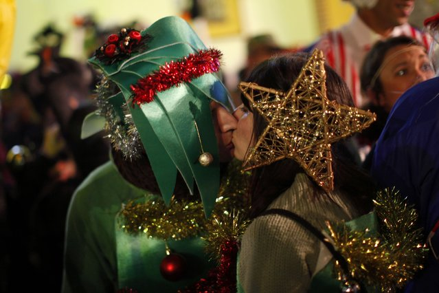 Revellers dressed up as Christmas trees kiss as they take part in New Year's celebrations in Coin, near Malaga, southern Spain, early January 1, 2015. (Photo by Jon Nazca/Reuters)