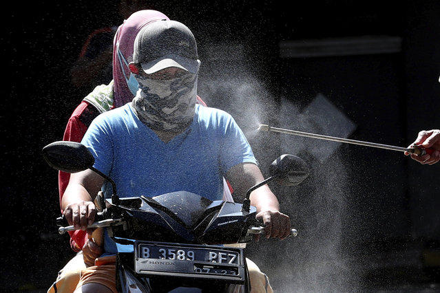 Motorists are sprayed with disinfectant in an attempt to curb the spread of coronavirus outbreak at the gate of a housing complex in South Tangerang, Indonesia, Tuesday, March 31, 2020. Indonesia will close its doors to foreign arrivals in an attempt to curb the coronavirus spread while the country plans to bring home more than a million nationals working abroad. (Photo by Tatan Syuflana/AP Photo)