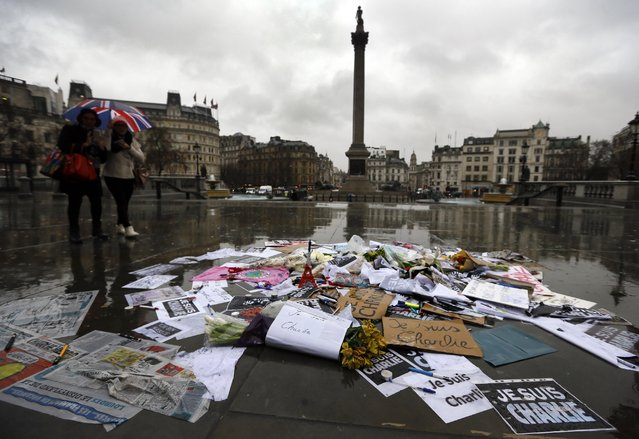 Flowers and pens and placards lie after being placed to show solidarity with those killed in an attack at the Paris offices of weekly newspaper Charlie Hebdo, in Trafalgar Square, London, Thursday, January 8, 2015. Masked gunmen stormed the Paris offices of a weekly newspaper that caricatured the Prophet Muhammad, methodically killing 12 people Wednesday, including the editor, before escaping in a car. It was France's deadliest postwar terrorist attack. (Photo by Kirsty Wigglesworth/AP Photo)