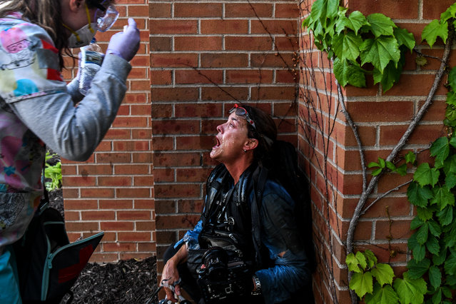 """A medic protestor assists a member of the media after police started firing tear gas and rubber bullets near the 5th police precinct during a demonstration to call for justice for George Floyd, a black man who died while in custody of the Minneapolis police, on May 30, 2020 in Minneapolis, Minnesota. Curfews were imposed in major US cities Saturday as clashes over police brutality escalated across America with demonstrators ignoring warnings from President Donald Trump that his government would stop the violent protests """"cold"""". (Photo by Chandan Khanna/AFP Photo)"""