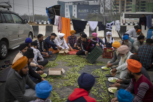 Farmers peel peas for community kitchen as they block a major highway in a protest against new farm laws while it rains at the Delhi-Uttar Pradesh state border, India, Monday, January 4, 2021. (Photo by Altaf Qadri/AP Photo)