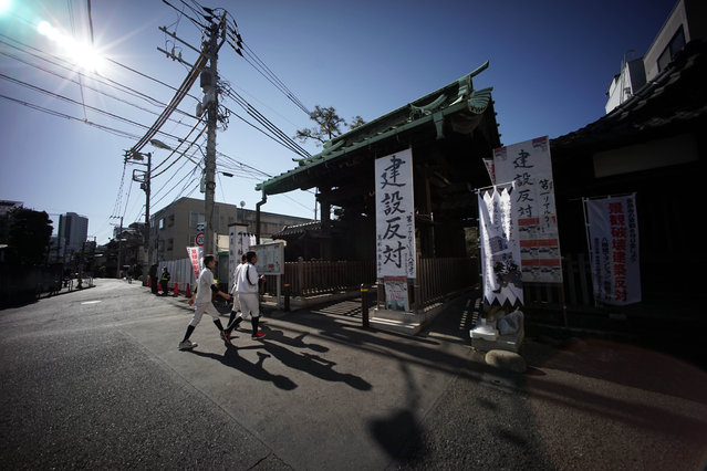 """In this January 8, 2015 photo, people walk near the protest banner-hoisted gate of Sengakuji temple, next to a new condo construction site in Tokyo. The banners read: """"Against the construction"""". (Photo by Eugene Hoshiko/AP Photo)"""