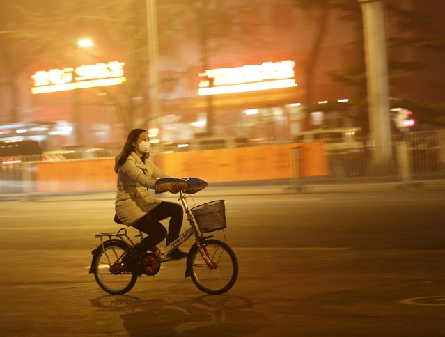 A woman wearing a protective mask rides a bicycle during an extremely polluted night as hazardous, choking smog continues to blanket Beijing, China December 1, 2015. (Photo by Kim Kyung-Hoon/Reuters)