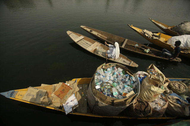 "A Kashmiri woman rows her boat past another loaded with plastic bottles and other waste collected from the Dal Lake as a cleanliness initiative on World Environment Day in Srinagar, Indian controlled Kashmir, Tuesday, June 5, 2018. ""Plastic pollution is a huge issue everywhere"", U.N. Environment chief Erik Solheim told The Associated Press in an interview. He praised India for its growing focus on environmental protection but also noted that while traveling in the country he'd seen ""some of the most beautiful scenic places, but destroyed by plastic pollution"". (Photo by A.M. Ahad/AP Photo)"