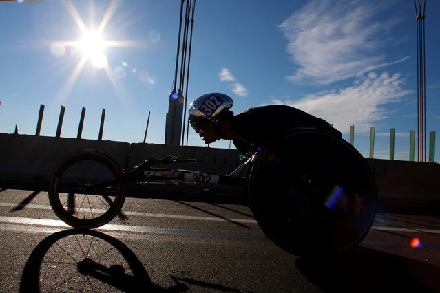 A participant taking part in the men's wheelchair division crosses the Verrazano–Narrows Bridge during the 2016 New York City Marathon in the Manhattan borough of New York City, NY, U.S. November 6, 2016. (Photo by Brendan McDermid/Reuters)