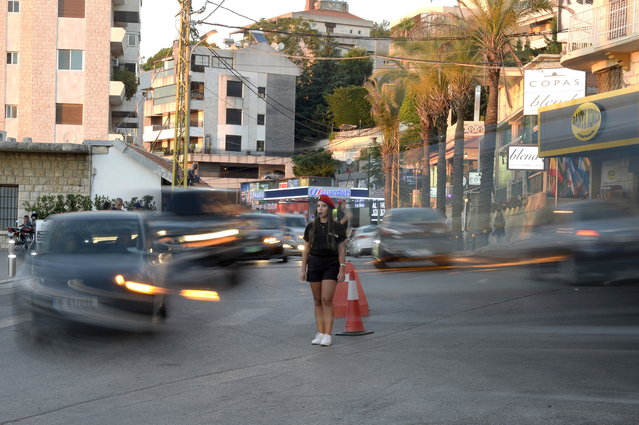 A slow shutter speed photo shows a Lebanese university student wearing municipality police costume regulates the traffic in the village of Brummana, east Beirut, Lebanon, 23 June 2018. (Photo by Wael Hamzeh/EPA/EFE)