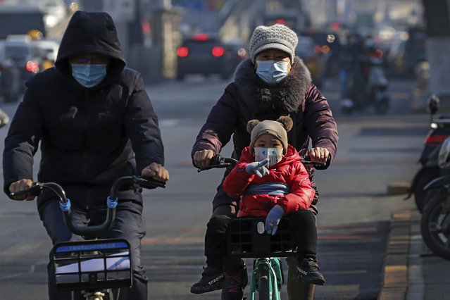 A woman and a child, both wearing face masks to help curb the spread of the coronavirus, ride a bike-sharing company bicycle through Beijing, Monday, February  8, 2021. China appears to have stamped out its latest coronavirus outbreaks centered on the northeast, reporting no new cases of local infection in its latest daily report. (Photo by Andy Wong/AP Photo)