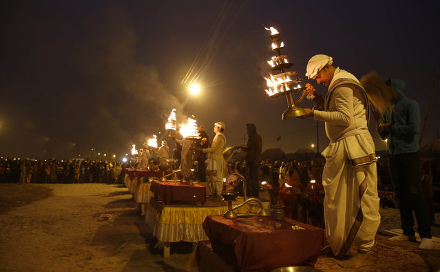 Hindu priests perform evening rituals at the Sangam, the confluence of the Rivers Ganges, Yamuna and mythical Saraswati, during the annual Magh Mela traditional fair in Allahabad, India, Saturday, January 17, 2015. (Photo by Rajesh Kumar Singh/AP Photo)