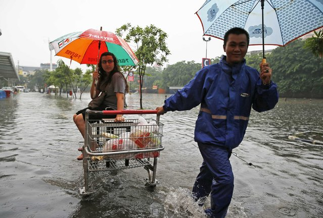 Lotte Mart customers make their way across the car park at the flooded Kelapa Gading business district in Jakarta, January 23, 2015. Floods inundated several areas of Jakarta after heavy rains in the capital city, local media reported on Friday. (Photo by Reuters/Beawiharta)