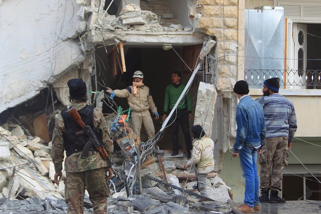 A civil defence member gestures towards a rebel fighter as they search for survivors at a site hit by what activists said were airstrikes carried out by the Russian air force in Idlib city, Syria December 20, 2015. (Photo by Ammar Abdullah/Reuters)